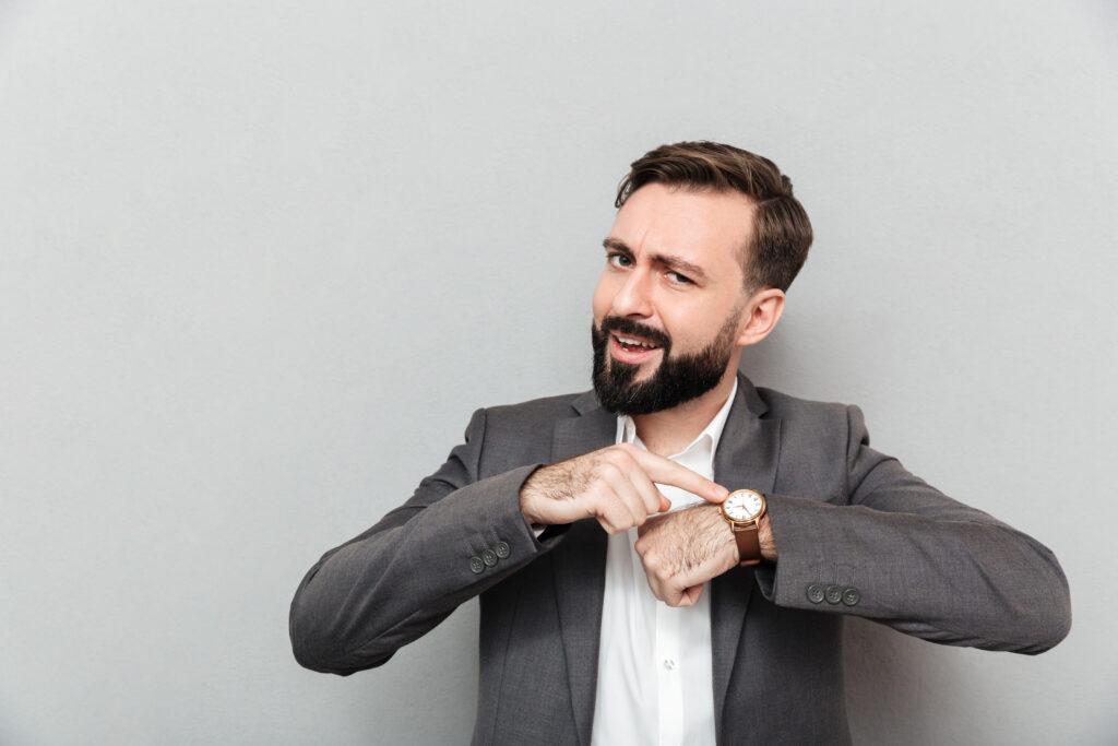Mężczyzna wskazuje na zegarek, przypominając o czasie na wykonanie audytu energetycznego przedsiębiorstwa.